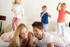 Family Relaxing Together In Bed Stock Photography