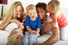 Family Relaxing Together In Bed Stock Image