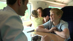 Family Relaxing On Train Journey. Family passing the time on train journey with digital tablet .Shot on Sony FS700 in PAL format at a frame rate of 25fps stock video footage