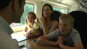 Family Relaxing On Train Journey. Family passing the time on train journey talking together .Shot on Sony FS700 in PAL format at a frame rate of 25fps stock video footage