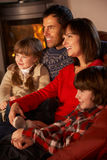 Family Relaxing Watching TV By Cosy Log Fire. On Ski Holiday Stock Photo