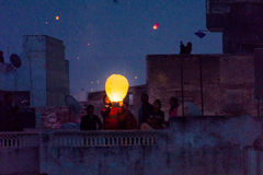 Family releasing a sky lantern from rooftop Stock Photo
