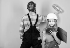 Family remodeling house. Little fathers helper. Father bearded man and daughter hard hat helmet uniform renovating home stock image