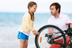 Family repairing bike Royalty Free Stock Image
