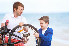 Family repairing bike Royalty Free Stock Photos