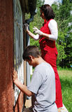 Family repairing house on the outside together. Stock Images