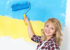 Family repairs. Happy woman makes repairs at home - painting wall at room. Portrait of smiling woman painting big Ukrainian flag on wall at home stock photo