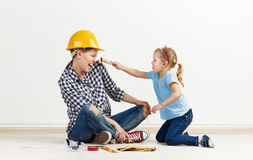 Family reparing house. Cute little girl with brush trying to paint her mum. Family house repair concept Stock Photos