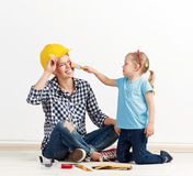 Family reparing house. Funny picture of laughing female in protective helmet and little girl with paintbrush. Concept of house remodeling and repair Royalty Free Stock Photos