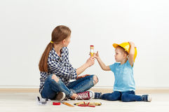 Family reparing house. Young family ready to make house renew. Adorable girl in yellow hardhat helping her mom to color the wall. Concept of home repair and Royalty Free Stock Photo