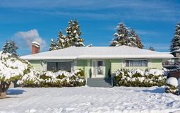 Family residential house with front yard in snow on winter sunny day. Family residential house with front yard in snow. North American house on winter sunny day royalty free stock image