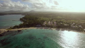Family on resort and Mauritius aerial view. Happy family with child bathing in clear water. Father controlling drone flying over Mauritius, its resorts and stock footage