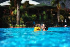 Family rest in pool. In the sunny day in the summer the boy in sun glasses and in a life jacket plays pool with mum Royalty Free Stock Image
