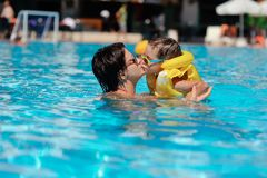 Family rest in pool. In the sunny day in the summer the boy in sun glasses and in a life jacket plays pool with mum Royalty Free Stock Images