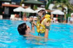 Family rest in pool. In the sunny day in the summer the boy in sun glasses and in a life jacket plays pool with mum Stock Photography