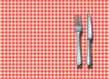 Family Restaurant. Place setting with a classic red and white checkered table cloth with a silver fork and knife as a symbol of fine italian food cuisine and Stock Images