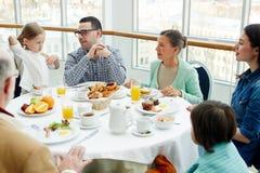Family in restaurant. Big family having talk by breakfast in restaurant royalty free stock photo