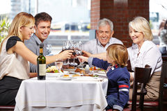 Family in restaurant clinking. Happy family in a restaurant clinking their glasses of wine and water stock photography
