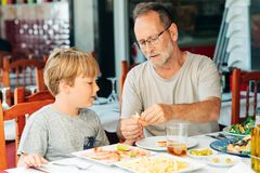 Family in the restaurant. Father and sun eating shrimps, summer vacation by the sea stock photo