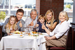Family in restaurant holding thumbs. Happy family congratulate in restaurant holding their thumbs up stock image