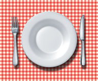 Family Restaurant Place Setting. Place setting for a family restaurant with a red and white checkered table cloth with a ceramic china plate silver fork and Stock Photo
