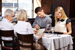 Family in restaurant reading menu. Family with in-laws in a restaurant reading the menu royalty free stock photo