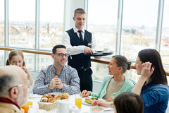 Family in restaurant. Young waiter serving family in restaurant royalty free stock photo