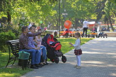 The family is resting on a bench in a park. Pyatigorsk, Russia - May 9, 2017: The family is resting on a bench in a park near the Lenin Square in Pyatigorsk stock photography