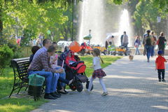 The family is resting on a bench in a park. Pyatigorsk, Russia - May 9, 2017: The family is resting on a bench in a park near the Lenin Square in Pyatigorsk stock photo
