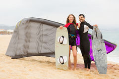 Family resting with kiteboard at the beach. Smiling family resting with kiteboard  at the beach Stock Image