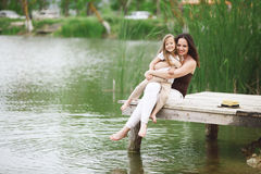 Family resting near pond. Happy young family with kids heaving fun near pond stock image