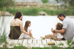 Family resting near pond royalty free stock photos