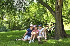 Family resting in a park. Family resting in summer park with bicycles stock images