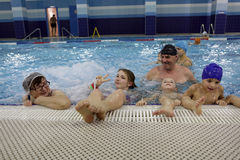 Family resting in pool Stock Photos