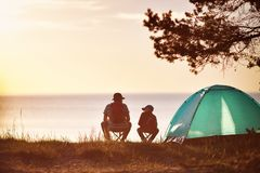 Family resting with tent in nature at sunset royalty free stock image