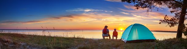 Family resting with tent in nature at sunset. Man and children near seaside royalty free stock images