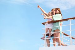 Family rests on yacht and indicates interesting Stock Photos