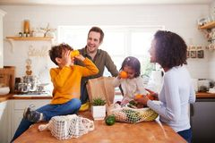 Free Family Returning Home From Shopping Trip Using Plastic Free Bags Unpacking Groceries In Kitchen Stock Images - 157268374