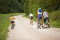 Family ride bikes on country road, outdoor in green environment Stock Image