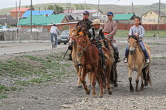 Family rides. KHARKHORIN, MONGOLIA, July 8, 2013 : A family rides in the streets of the town before Naadam festival. Half of mongolian population has a nomadic stock photography