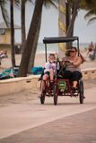 A family rides a tricycle on the boardwalk by the beach. stock images