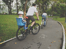 Family riding bicycle in the park on holiday Concept Stock Images