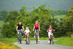 Family riding bicycles. Family with children having a weekend excursion on their bikes on a summer day