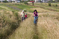 Family riding a bicycles in the meadow Royalty Free Stock Images