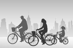 Family riding bicycles silhouettes Stock Photos