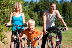 Family riding bicycles for sport. Family with child on their bikes on a summer day in sport outfit, they are exercising Royalty Free Stock Photos