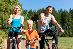 Family riding bicycles for sport. Family with child on their bikes on a summer day in sport outfit, they are exercising Royalty Free Stock Image