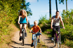 Family riding bicycles for sport. Family with child on their bikes on a summer day in sport outfit, they are exercising Stock Photo