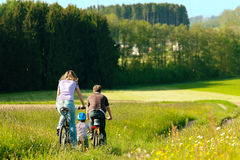 Family riding bicycles in summer Stock Photos