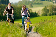 Family riding bicycles in summer. Family on a trip with their bicycles in a wonderful scenery, since their son is so young he is riding a training bike Stock Photography